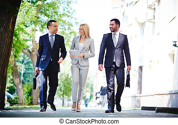 Image of elegant colleagues walking and discussing business matters on the move