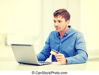 business, online banking, internet shopping concept - smiling man with laptop and credit card at home