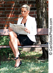 Business outdoor - Business women working reading newspaper