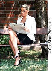 Business outdoor - Business women working reading newspaper