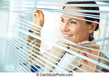 Business outlook - Smiling business woman looking out of the...