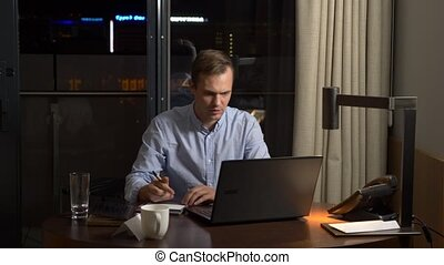 business, overwork, deadline and concept of people - a man working on a laptop at night. 4k