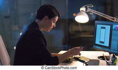 businesswoman with computer eating at night office -...