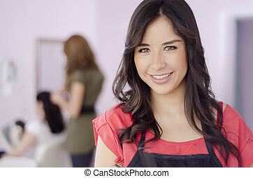 Cute female business owner greeting customers in a hair and beauty salon