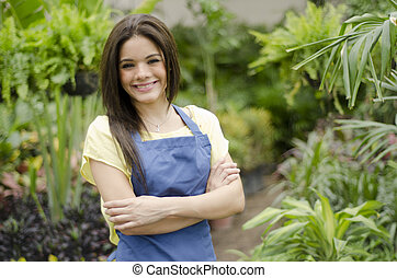 Business owner greeting customers - Cute female garden owner...