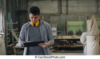 Business owner man walking in wood workshop with laptop ...