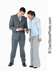 Business partner having a look at a clipboard together against a white background