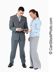 Business partner looking at clipboard together against a white background