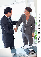Business partner shaking hands after closing a deal - Young...