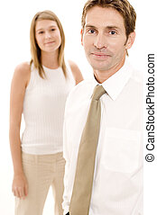 A businessman stands in front of a female colleague (shallow depth of field)