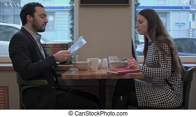 Business partners discuss documents during lunch at cafe