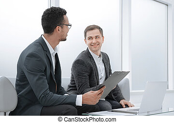 business partners discussing business documents in the banking lobby