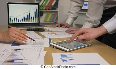 Business partners discussing economic situation of company at meeting in office. Group of men and women viewing graph statistics using tablet, laptop and papers. Coworker teamwork concept. Close up. Slow motion ready, 4K at 59.94fps.