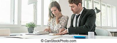 Business partners doing calculations on an adding machine or calculator