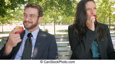 Business partners eating ripe fruit while sitting on a park bench hand held
