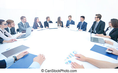 business partners gathered round a table and discuss the financi