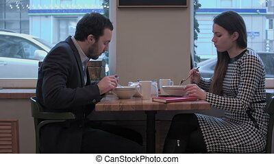 Business partners have lunch at cafe use smartphones