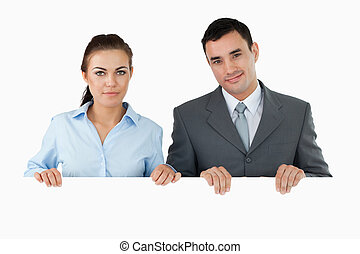 Business partners holding sign against a white background