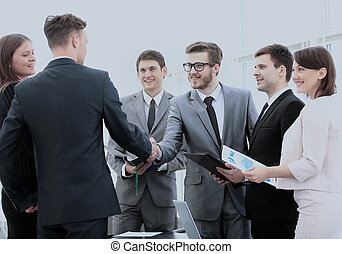 business partners in the presence of a business team shake ...