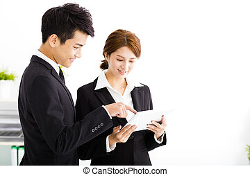 business partners looking at business document in tablet