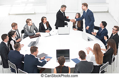 business partners shake hands at the talks near the round...