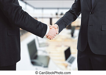 Business partners shake hands in the office