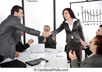 Business partners shaking hands after making deal while their co-workers applauding
