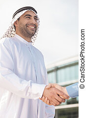 Business partners shaking hands. Low angle view of Arab...