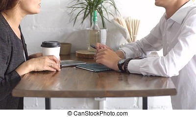Business partners sitting together in cafe, using smart phones and talking at coffee break.