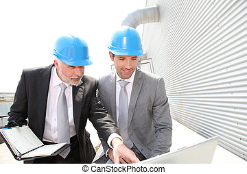 Business partners working on industrial site