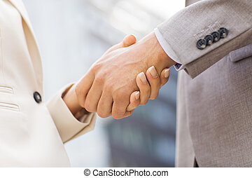 close up of business couple shaking hands - business,...