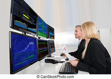 Business People Analyzing Data Displayed On Computer Screens