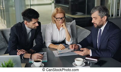 Business people analyzing financial documents working in cafe during lunch break