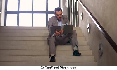 businessman with folder sitting on stairs - business, people...