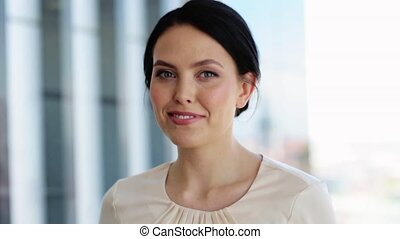 face of happy smiling young woman at office