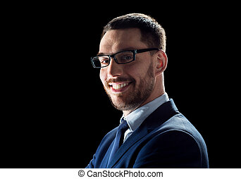 smiling businessman in glasses over black