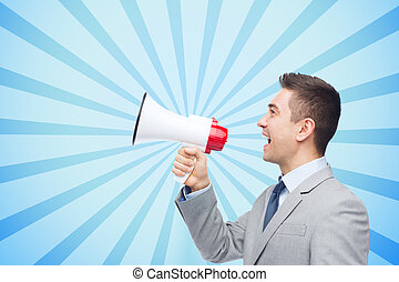 business, people and public announcement concept - happy businessman in suit speaking to megaphone over blue burst rays background