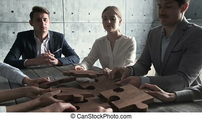 Business people assembling wooden puzzle on work table, teamwork concept