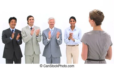 Business people applauding a woman against a white...