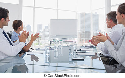 Business people applauding at a blank whiteboard during a...