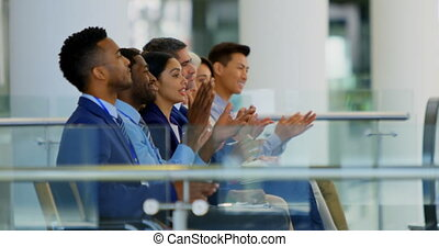 Side view of multi ethnic business people sitting and applauding in the business seminar 4k