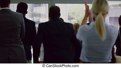 Rear view of Business people applauding male speaker in a business seminar. They are attending a business seminar 4k