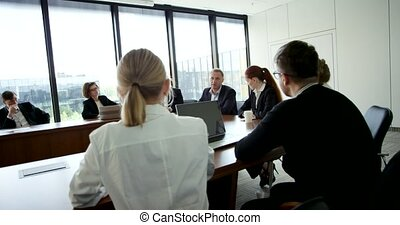 Business People at corporate meeting sitting around table...