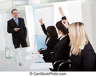 Business people at presentation raising hands - Group of ...