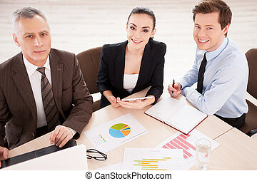 Business people at work. Top view of three confident business people in formalwear working together while sitting together at the table and smiling