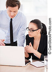 Business people at work. Two confident business people discussing something while looking at the laptop