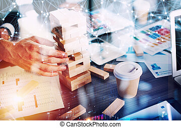 Business people build a tower of wooden bricks in the office. Concept of teamwork and partnership. double exposure with light effects