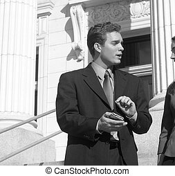 businessman is facing businesswoman pointing to pda while talking on steps of courthouse