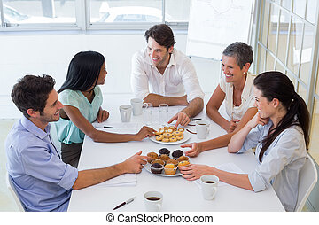 Business people chat while eating m