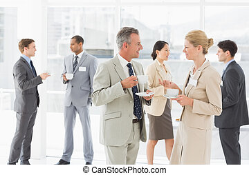 Business people chatting at a conference in the office